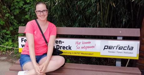 """Evelyn Förg, Mitarbeiterin unserer Buchhaltungs-Abteilung, freut sich über die neue """"Perfecta-Bank"""" im Zoo Augsburg."""